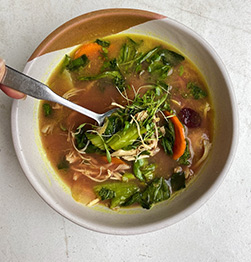 healthy golden bone broth with chicken and veg in Houston at Vibrant